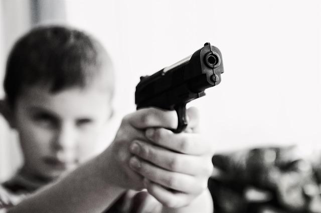 kluk s pistolí