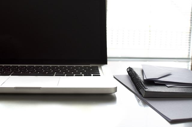 počítač notebook a vedle něj obálky a bloček